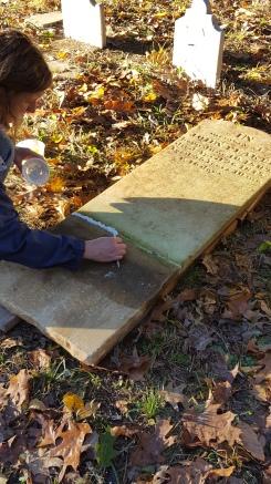 Kristin Cardi repairs a headstone